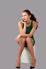 Sad thoughtful girl sitting alone