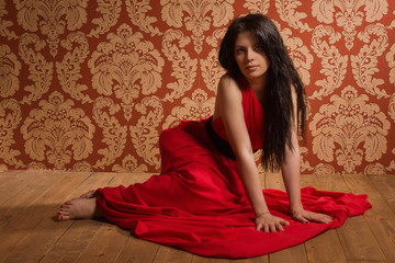 Fashionable brunette in a long red dress