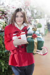 Young woman carries her Christmas gifts