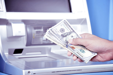 Hand holding money in front of ATM -retro style lighting effect