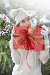 dreamy woman, holding her christmas gift