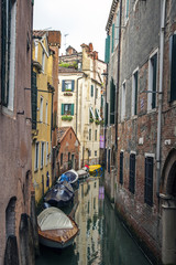 Boats outside apartments on a canal in venice, Italy