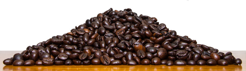Roasted coffee beans laying on a pile of wood