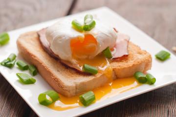 Delicious breakfast. Eggs benedict with ham on toast.