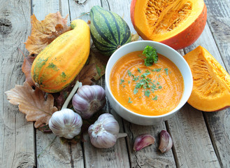 Bowl with pumpkin cream soup with parsley and whole pumpkin