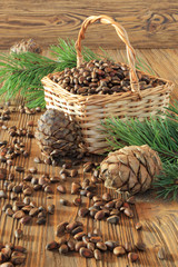 Cedar nuts in a wicker basket on a wooden table