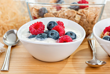 Bowl with berries and yoghurt on a bamboo mat close up