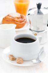 breakfast with coffee, sweet bun, fresh cream and orange juice