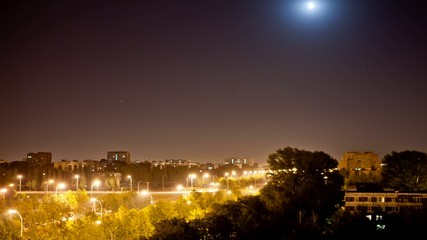 time lapse night city with a moving moon until dawn