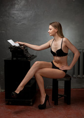 Beautiful girl in black lingerie working on a typewriter