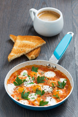 fried quail eggs in tomato sauce with toasts and coffee