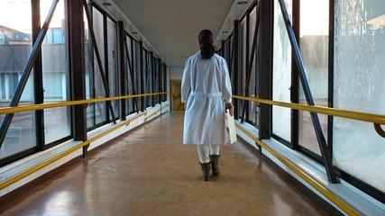 Médico atravesando pasarela de hospital