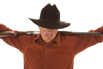 cowboy with arms on gun over shoulders head down