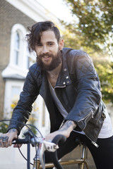 Young man in his 20s or early 30s with bicycle