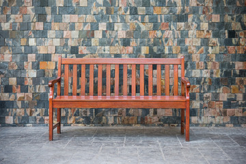 Wood bench against  brick wall.
