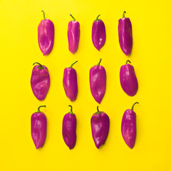 bright peppers and one pear on a yellow background