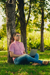 Young man Working in the Park with Laptop Computer