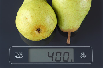 Two green pears on kitchen scale