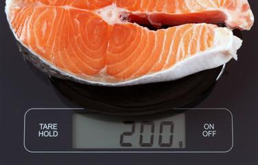 Steak of salmon fish on kitchen scale