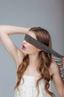 Hide and Seek. Woman Holding a Strap on her Face. Puzzle