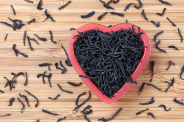 Black tea leaves in a heart bowl