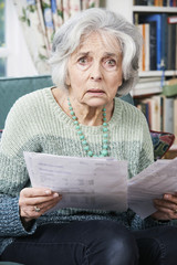 Senior Woman Going Through Bills And Looking Worried