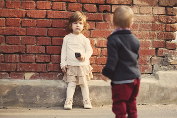 little boy and girl playing with phone