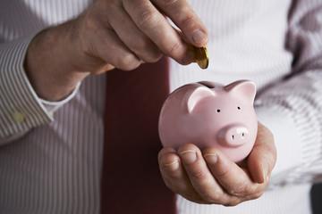 Businessman Putting Coin Into Piggy Bank