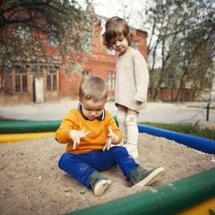 boy and girl playing in sandbox