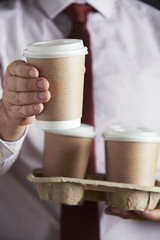 Businessman Holding Tray Of Takeaway Coffee