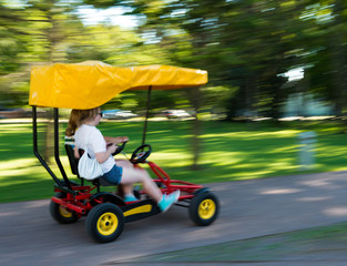 Girls racing in a pedal cart