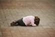 Leinwanddruck Bild - crying girl lying on asphalt