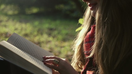 Closeup of beautiful girl reading a book in the park at fall.
