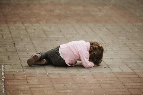 Leinwanddruck Bild crying girl lying on asphalt