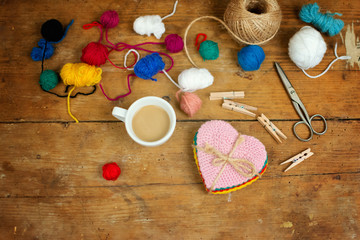 Cup of coffee and various wool yarns on wooden surface