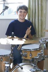 Boy Playing Drum Kit At Home