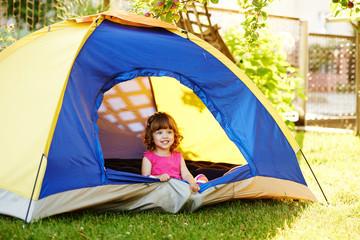little beautiful girl sitting in tent