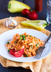 risotto with chicken and vegetables on a plate with fork