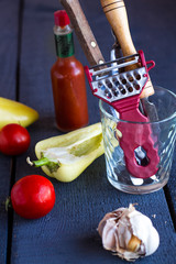 cutlery, raw vegetables on dark wooden board, vertically
