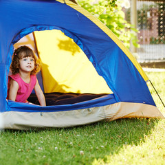 little beautiful girl sitting in tent