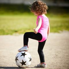cute little girl plays football