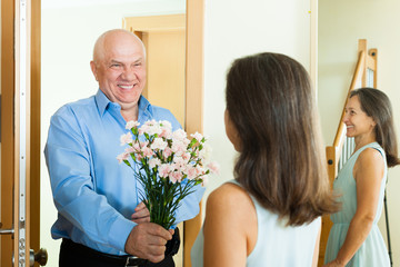 Mature man giving   flowers to  woman