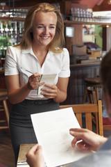 Waitress In Restaurant Taking Order From Customer