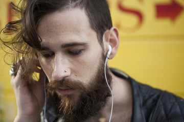 Young man in his 20s or early 30s in cafe with earphones