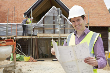 Architect On Building Site Looking At House Plans