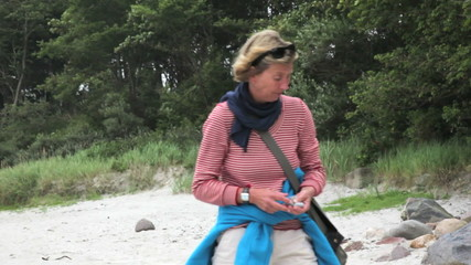 adult woman collecting sea shells at the beach