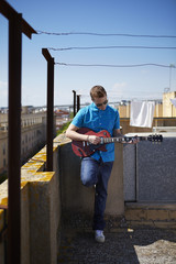 Young man plays electric guitar on roof terrace