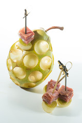 Appetizer. Creative cuisine. Prosciutto with pear on a white