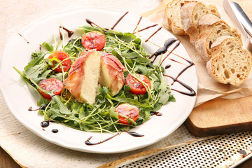 Mozzarella baked in ham of Parma with arugula
