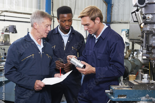 Team Of Engineers Having Discussion In Factory - 71237935